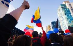 Quito, Ecuador - 7 de abril de 2016: Grupo de personas que detiene muestras de la protesta, los globos con policía y a los period Foto de archivo libre de regalías
