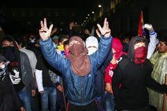 Quito, Ecuador - 27 de agosto de 2015: Manifestantes jovenes que llevan máscaras y ropa que cubre sus caras que marchan a través  Foto de archivo