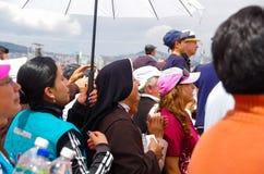 QUITO, ECUADOR - 7 DE JULIO DE 2015: En el medio de mil personas que una monja está rogando debajo del sol, policía está detrás d Imagenes de archivo