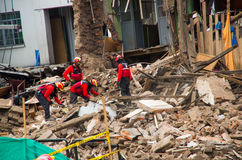 Quito Ecuador - December 09, 2016: En oidentifierad grupp av firemans och att göra ren skadeområdet och förstörelsen, skräp Fotografering för Bildbyråer