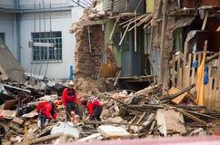 Quito Ecuador - December 09, 2016: En oidentifierad grupp av firemans och att göra ren skadeområdet och förstörelsen, skräp Royaltyfria Foton