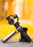 QUITO, ECUADOR- DECEMBER 22, 2017: Osmo Mobile gimbal, new generation of electronic stabilizer over a wooden table in a. Blurred forest background royalty free stock photos