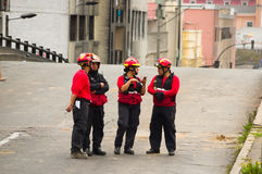 Quito, Ecuador - December 09, 2016: An unidentified group of firefighter`s team with equipment, talking and using their. Cellphones in the streets Stock Photo