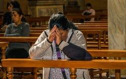 QUITO ECUADOR, FEBRUARI 22, 2018: Inomhus sikt av oidentifierat folk som ber inom av den laCatedral kyrkan i Quito` s royaltyfri fotografi