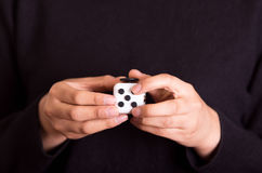 Quito, Ecuador - February 10, 2017: Fidget Cube stress reliever manipulated with both hands.  Royalty Free Stock Images