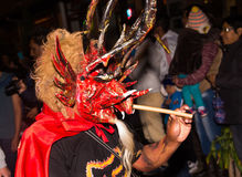 Quito, Ecuador - february 02, 2016: An unidentified man dressed up participating in the Diablada, with a demon mask in. His head with a stick in his hand Stock Photography