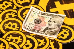 Quito, Ecuador - Januari 31, 2018: Binnenmening van vele Gouden Bitcoin-emblemen onder een tien dollarsrekening Bitcoin Royalty-vrije Stock Fotografie