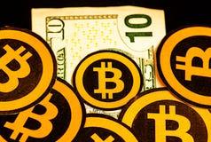 Quito, Ecuador - Januari 31, 2018: Sluit omhoog van vele Gouden Bitcoin-emblemen over een tien dollarsrekening Bitcoincryptocurre Stock Fotografie