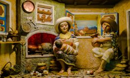 QUITO, ECUADOR, JANUARY 31, 2018: Close up of a clay figures of a indigenous woman with baby in her arms inside of. Typical hut, located inside of San Francis stock images