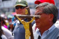 QUITO, ECUADOR - 7. JULI 2015: Alter Mann, der ein großes Kreuz mit Jesus-Körperdarstellung, Masse Papstes Francisco mit Losen hä Stockfotografie