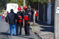 QUITO, ECUADOR - 7. JULI 2015: Ein Mann, der mit zwei Feuerwehrmännern auf der Straße, Leute hereinkommen zu Papst Francisco spri Stockfotografie