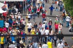 QUITO, ECUADOR - 7. JULI 2015: Leute zwischen den Linien, gehend in eine lange Straße Lebensmittelladen auf den Seiten Stockfotos