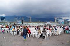 QUITO ECUADOR - JULI 7, 2015: Massor av människor som sitter på vita stolar som waitting påven Francisco, samlas Första gång för Royaltyfri Fotografi