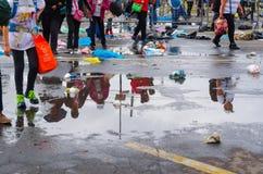 QUITO ECUADOR - JULI 7, 2015: Når han har regnat vattenpölstaget på gatan, skuggar folket på dem, och gå på Royaltyfria Foton