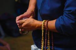 QUITO, ECUADOR - JULI 7, 2015: Oude handen met gebedparels van verschillende kleuren, de massa van pausfrancisco op Ecuador Stock Foto's