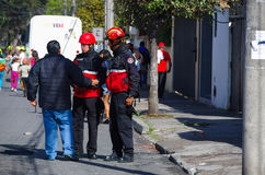 QUITO, ECUADOR - JULY 7, 2015: A man speaking with two firefighters on the street, people entering to pope Francisco Stock Photography