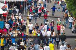 QUITO, ECUADOR - JULY 7, 2015: People between lines, walking in a long street. Food shops on the sides Stock Photos