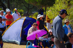 QUITO, ECUADOR - JULY 7, 2015: People sitting and hearing on the grass, pope Francisco mass in Ecuador. Tent in the back Stock Image