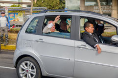 QUITO, ECUADOR - JULY 7, 2015: Pope Francisco in a grey car saying hello to people on the streets, body guards with him Stock Photo