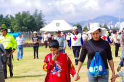QUITO, ECUADOR - JULY 7, 2015: Selective focus for a woman with a white hat and his son in her hand. First aids and Royalty Free Stock Photos