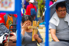 QUITO, ECUADOR - JULY 7, 2015: A woman selling wooden crosses for the mass, sunny day at pope Francisco mass in Ecuador Royalty Free Stock Photo