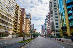 QUITO, ECUADOR - 7 LUGLIO 2015: Viale importante nella città, alte costruzioni con gli alberi nel giorno medio e soleggiato Fotografia Stock