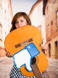 Quito, Ecuador - Maart 11, 2016: De jonge vrouw die een gitaar met groot als hand houden drukte bovenkant - neer, in vaag Royalty-vrije Stock Fotografie