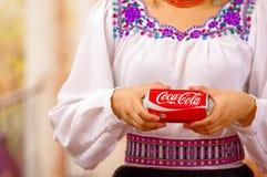 Quito Ecuador - Maj 06, 2017: Bära för ung kvinna infödd kläder och peka in från av henne en cola Royaltyfri Fotografi