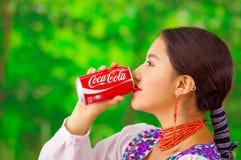 Quito Ecuador - Maj 06, 2017: Härlig ung infödd kvinna som dricker en cola i en skogbakgrund Royaltyfri Foto