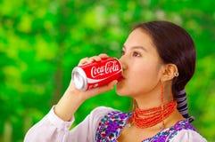 Quito Ecuador - Maj 06, 2017: Härlig ung infödd kvinna som dricker en cola i en skogbakgrund Arkivfoton