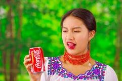 Quito Ecuador - Maj 06, 2017: Härlig ung infödd kvinna som dricker en cola och göra en ful framsida i en skog Arkivbild