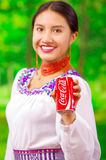 Quito Ecuador - Maj 06, 2017: Le att bära för ung kvinna infödd kläder och att peka in från av henne en cola Royaltyfria Foton