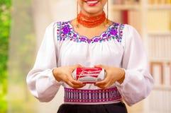 Quito Ecuador - Maj 06, 2017: Le att bära för ung kvinna infödd kläder och att peka in från av henne en cola Royaltyfri Foto