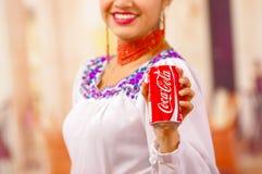 Quito Ecuador - Maj 06, 2017: Le att bära för ung kvinna infödd kläder och att peka in från av henne en cola Arkivfoto