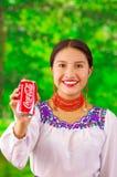 Quito Ecuador - Maj 06, 2017: Le att bära för ung kvinna infödd kläder och att peka in från av henne en cola i a Royaltyfri Bild