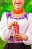 Quito Ecuador - Maj 06, 2017: Le att bära för ung kvinna infödd kläder och att peka in från av henne en cola i a Royaltyfri Fotografi