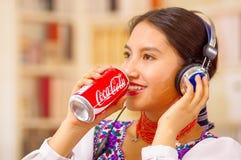 Quito Ecuador - Maj 06, 2017: nätt ung infödd kvinna som dricker en cola, medan hon använder hörlurar Arkivbilder