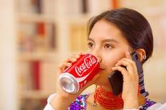 Quito Ecuador - Maj 06, 2017: nätt ung infödd kvinna som dricker en cola, medan hon använder hennes mobiltelefon Royaltyfria Bilder