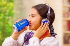Quito Ecuador - Maj 06, 2017: nätt ung infödd kvinna som dricker en pepsi, medan hon använder hörlurar Arkivbild