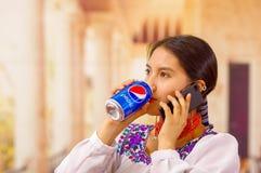 Quito Ecuador - Maj 06, 2017: nätt ung infödd kvinna som dricker en pepsi, medan hon använder hennes mobiltelefon Royaltyfria Foton
