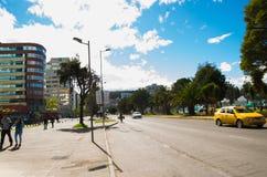 QUITO ECUADOR - MAJ 06 2016: Oidentifierat folk som går i mainstreeten i NNUU-aveny med några byggnader, bilar och Fotografering för Bildbyråer