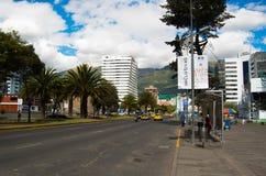QUITO ECUADOR - MAJ 06 2016: Oidentifierat folk som waling i mainstreeten i NNUU-aveny med några byggnader, bilar och Royaltyfri Bild