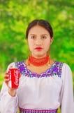 Quito Ecuador - Maj 06, 2017: Tokig ung infödd kvinna som rymmer en cola i hennes händer i en skogbakgrund Arkivbilder