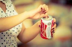 Quito Ecuador - Maj 06, 2017: Ung kvinna som öppnar ett uppfriskande Budweiser öl i en suddig bakgrund, tappningeffekt Royaltyfri Bild