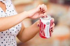 Quito Ecuador - Maj 06, 2017: Ung kvinna som öppnar ett uppfriskande Budweiser öl i en suddig bakgrund, tappningeffekt Fotografering för Bildbyråer