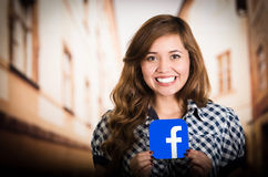 Quito, Ecuador - March 11, 2016: Close up of beautiful woman holding a sticker facebook icon with both hands. Largest Royalty Free Stock Image