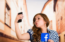 Quito, Ecuador - March 11, 2016: Woman taking a selfie with modern mobile phone and holding a sticker facebook icon Stock Image