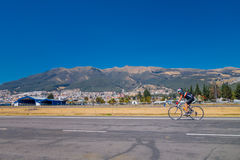 QUITO, ECUADOR - MARZO 23, 2015: On the road an unidentified cyclist training and great view behind him, sunny day Royalty Free Stock Images