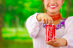 Quito, Ecuador - May 06, 2017: Beautiful smiling indigenous woman drinking a coke in a forest background Stock Photography
