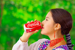 Quito, Ecuador - May 06, 2017: Beautiful young indigenous woman drinking a coke in a forest background Royalty Free Stock Photo